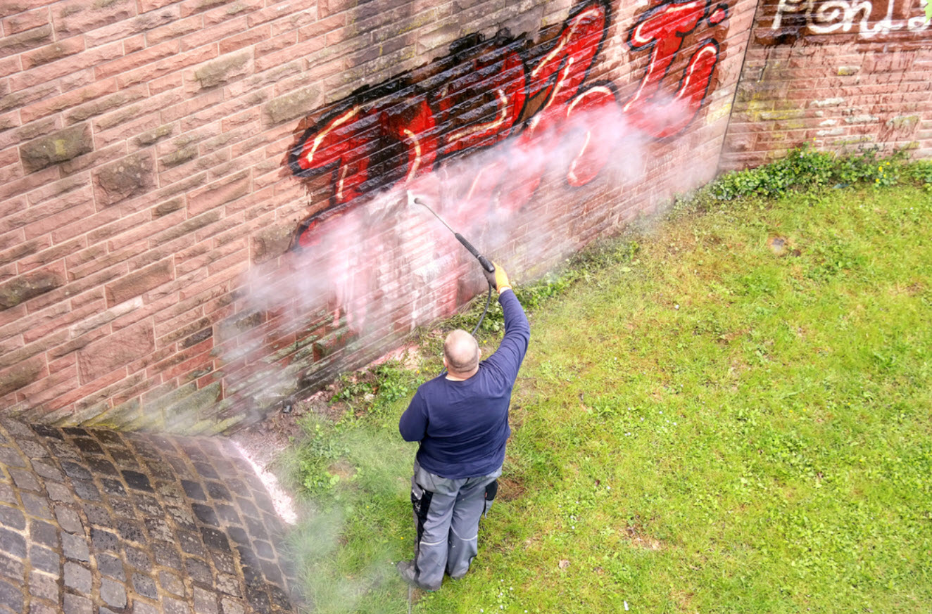 Removing graffiti using power washing in Richardson TX.